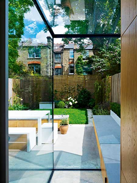A concrete window seat in this London home has been designed to appear as if it continues out seamlessly to the garden thanks to a divide of frameless glazing