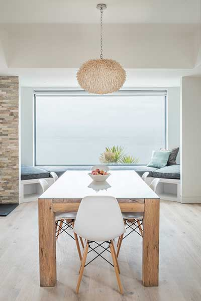 A window seat built into a nook within the dining area of this self build on the coast offers unobstructed views of the sea