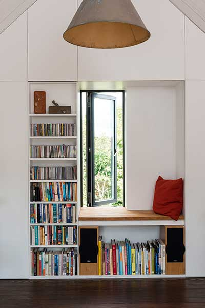 A window seat complete with bookcase has been built into wall of this conversion project. The adjacent bookcase makes the seat an ideal spot to read while enoying views of the outdoors