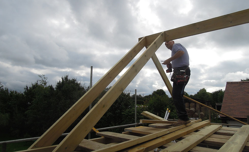 Man fixing timber rafters on a roof