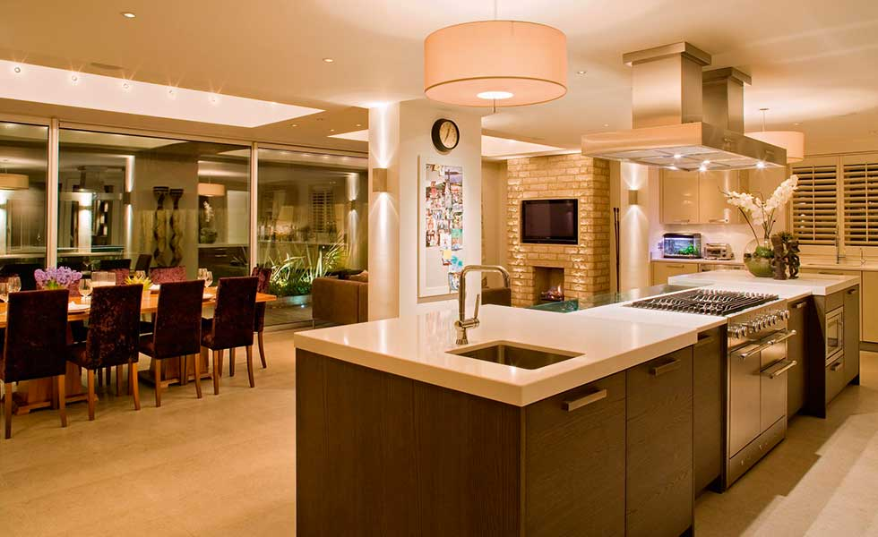 This open plan kitchen diner features lighting designed by John Cullen