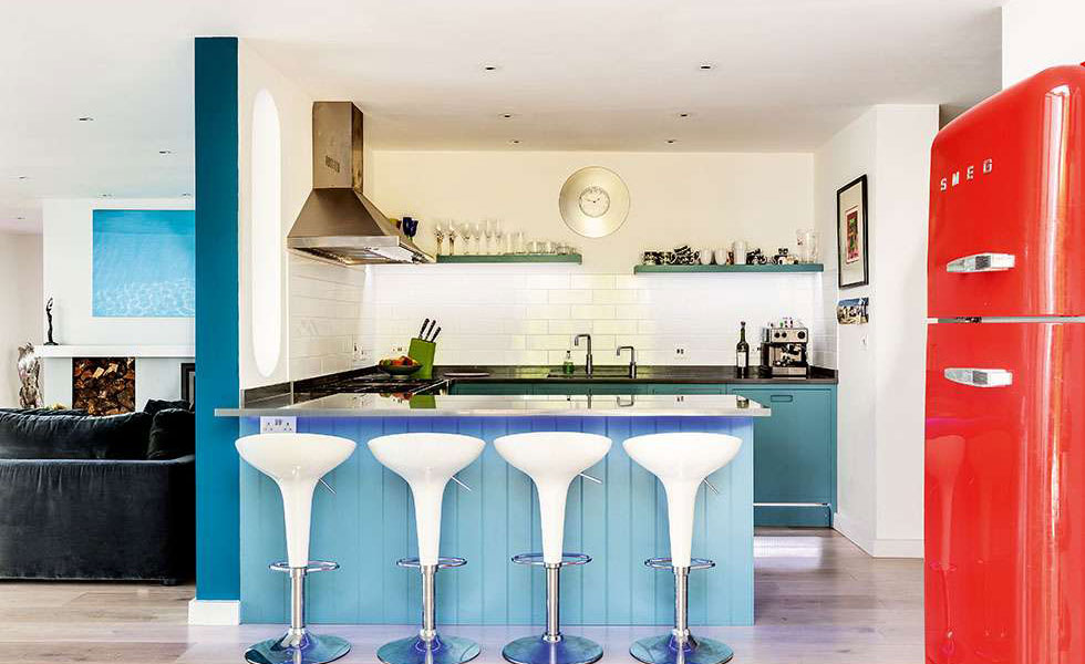 blue kitchen with partition red fridge