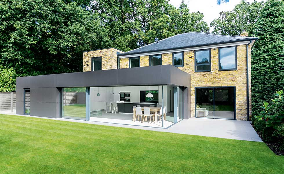 A stark contrast against the existing home's London stock brick façade, the new rear extension has been clad in Marley Eternit's fibre cement cladding — the colour of which is mirrored in the powder-coated aluminium window frames