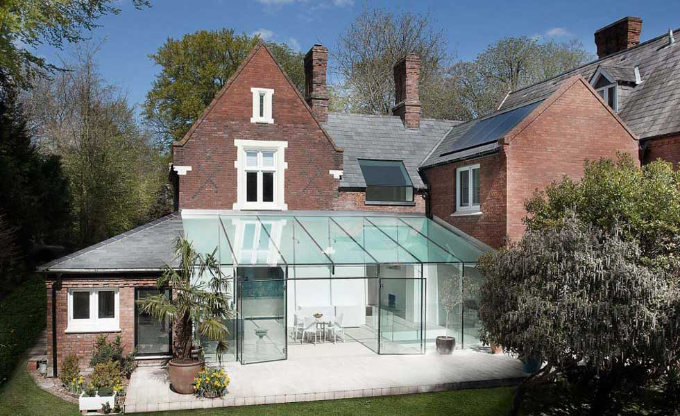 A frameless glass extension to this period property provides a stark contrast between old and new