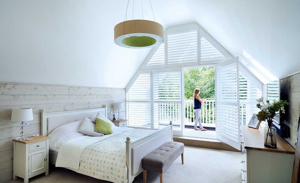Voluminous vaulted ceilings add wow factor to the master bedroom in this New England remodel. French doors open out to a covered balcony to enjoy the garden views in all weather