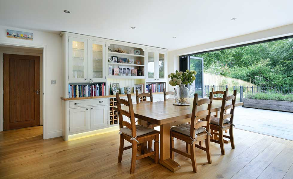 Bespoke joinery provides an ideal place to display wares in the dining area. Bifold doors open out onto the BBQ deck