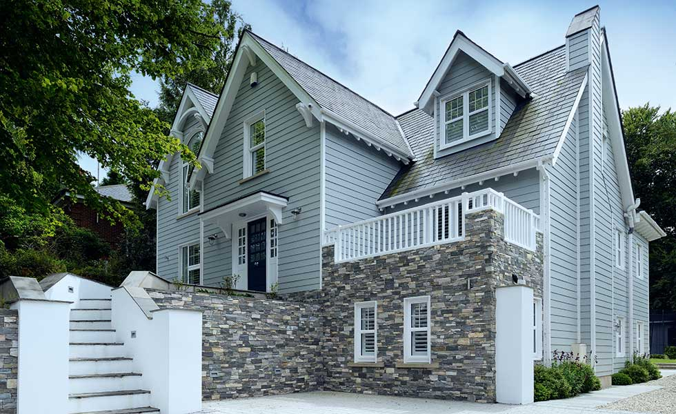 Weatherboard cladding, stone and a gabled roof all add to the New England style of this remodel on the coast