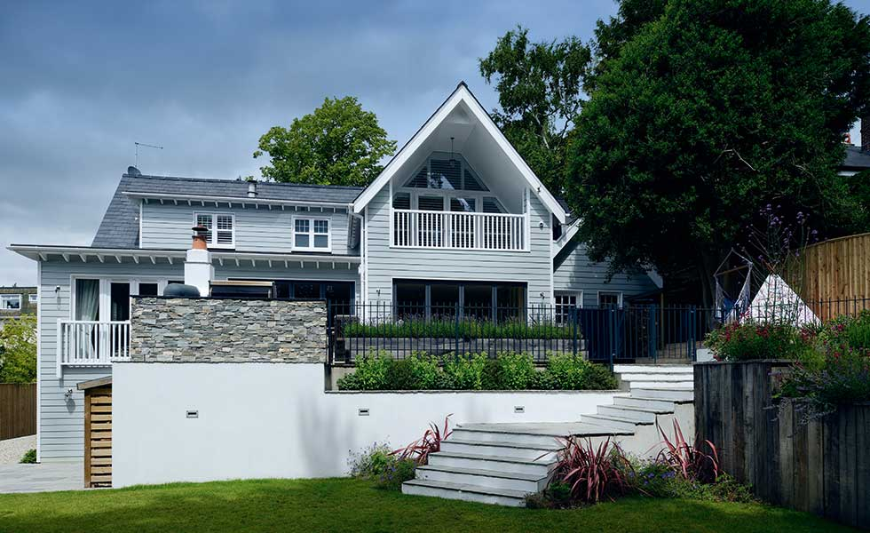 Weatherboard cladding and steep gables lend to the New England American style of this remodel