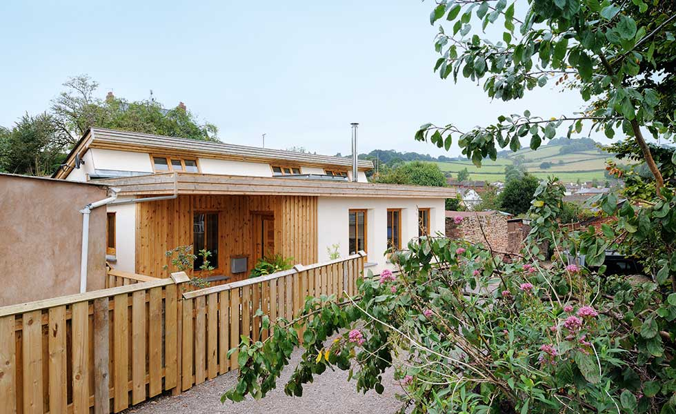 This low cost sustainable home is clad in render and timber and was completed for just £95,000 on a DIY basis