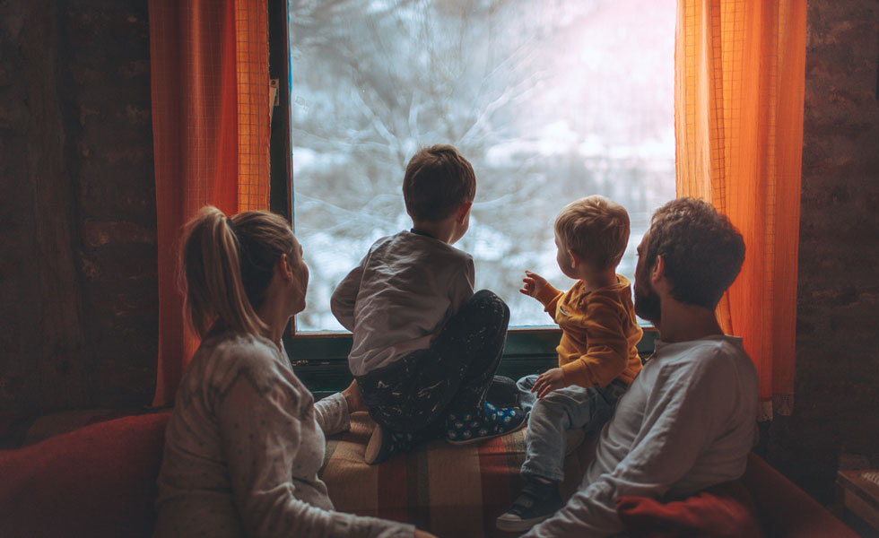 Family huddled together in front of a window