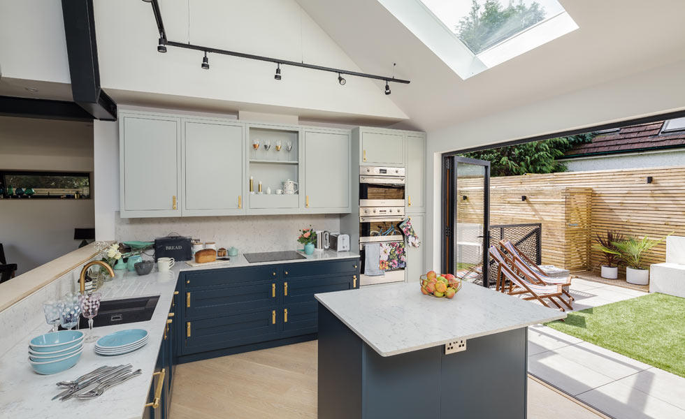 kitchen with dark blue cabinets, an island and bi fold doors