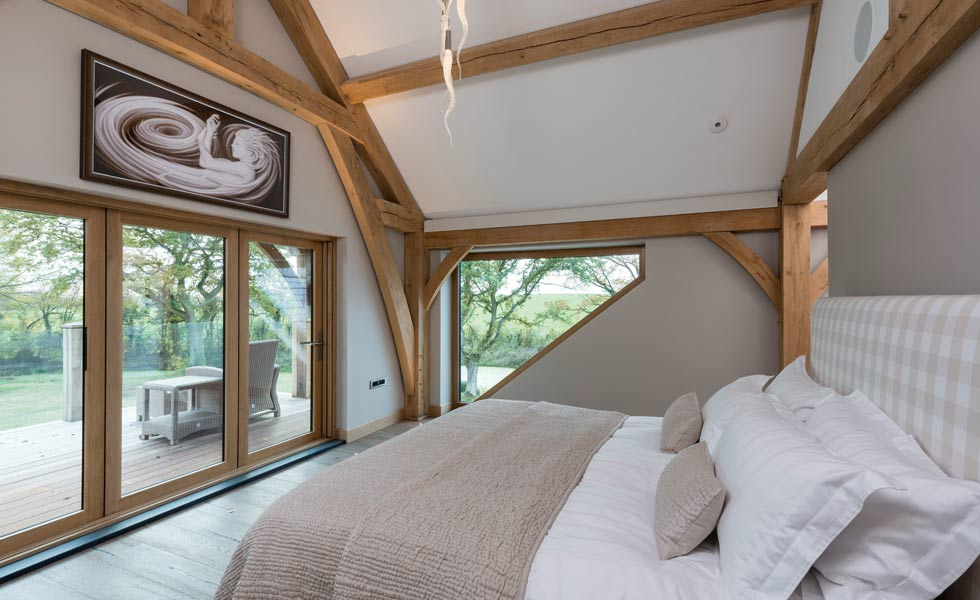 master bedroom with oak beams and bifold doors