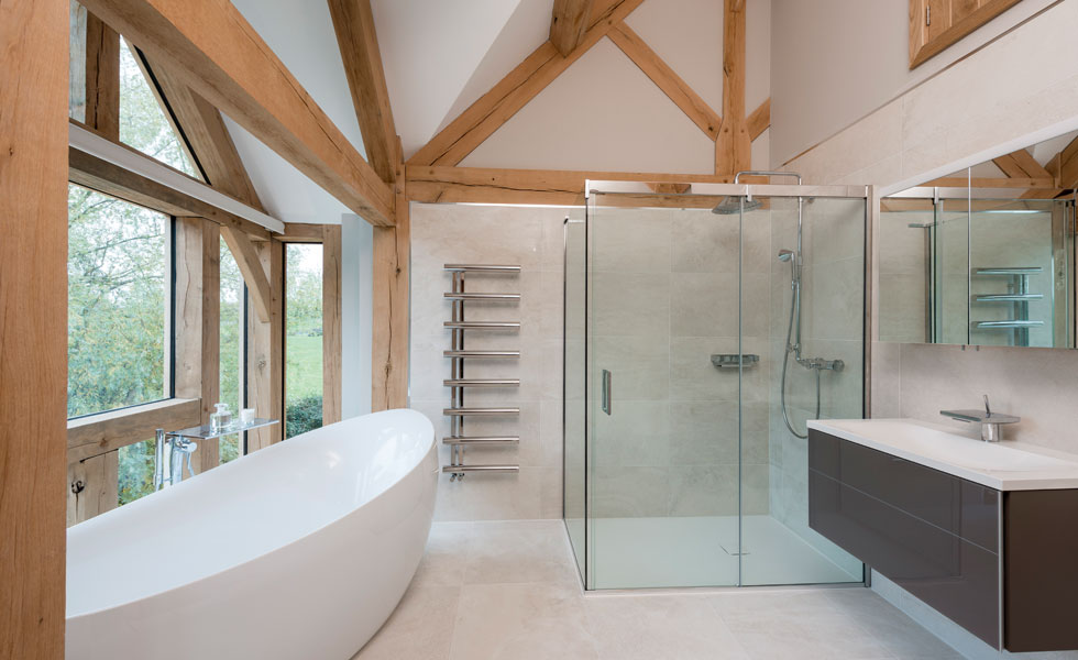 Master en suite with white bathtub and walk in shower and exposed oak beams