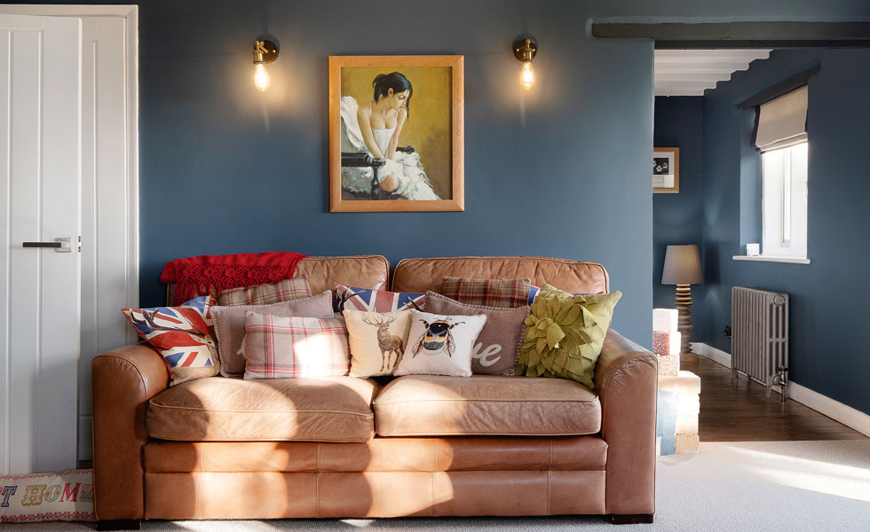 Dark blue living room with tan leather sofa