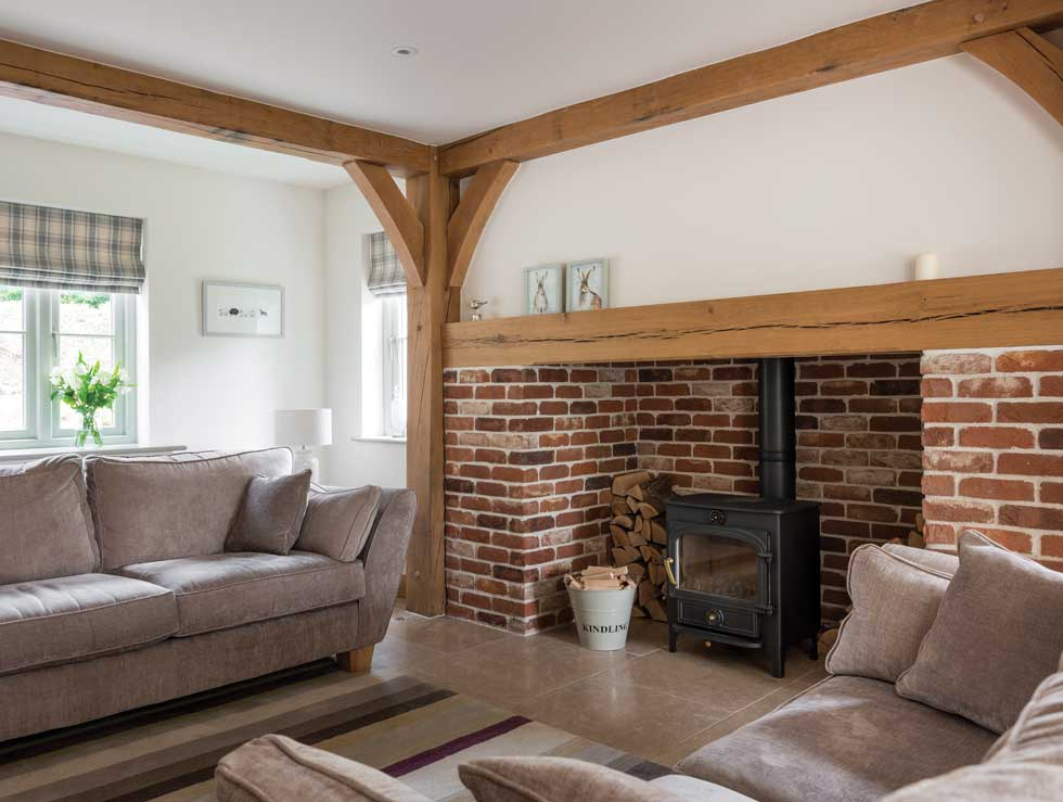 living room with exposed oak beams, brick inglenook fireplace and woodburning stove