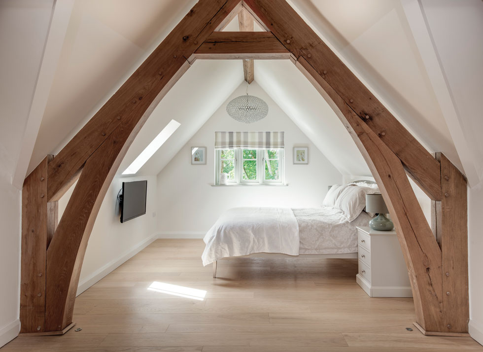 bedroom with exposed oak frame and oak flooring
