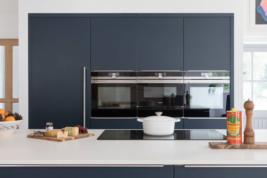 White and navy contemporary kitchen with built-in ovens