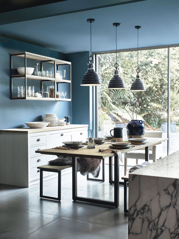 Dark, moody tones, like the blue of this kitchen, help create a cosy ambience