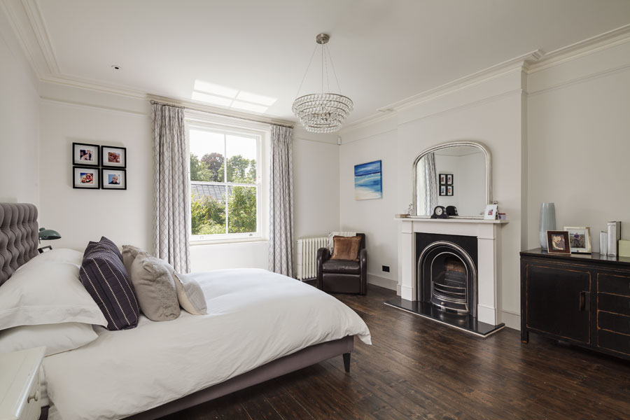 Master bedroom with period fireplace and timber flooring
