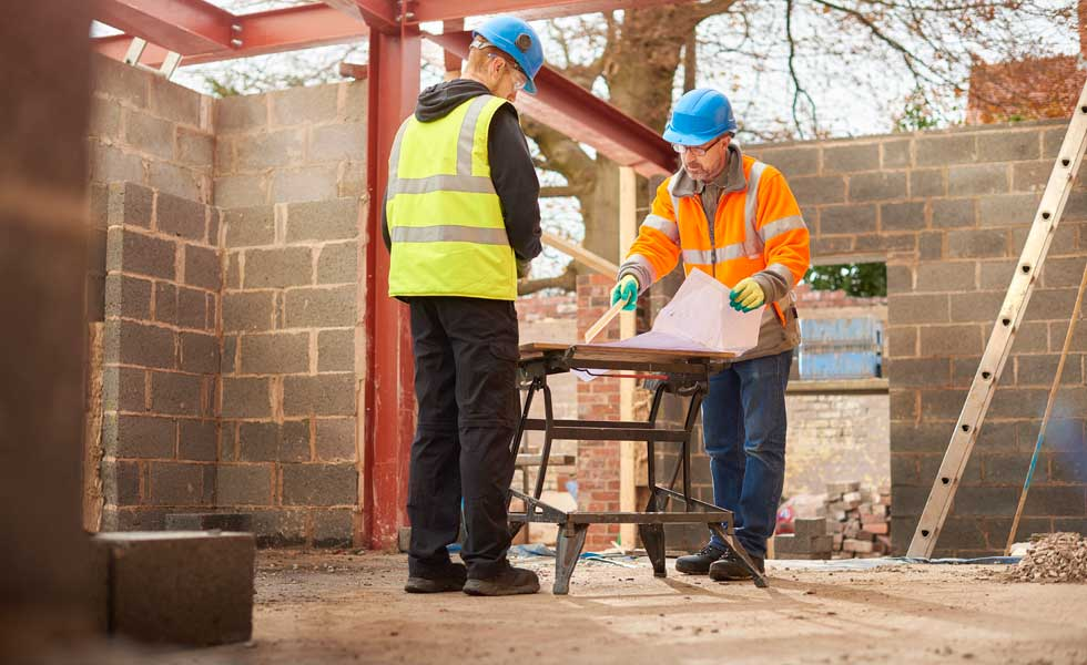 two people in hard hats on site of a housebuilding project