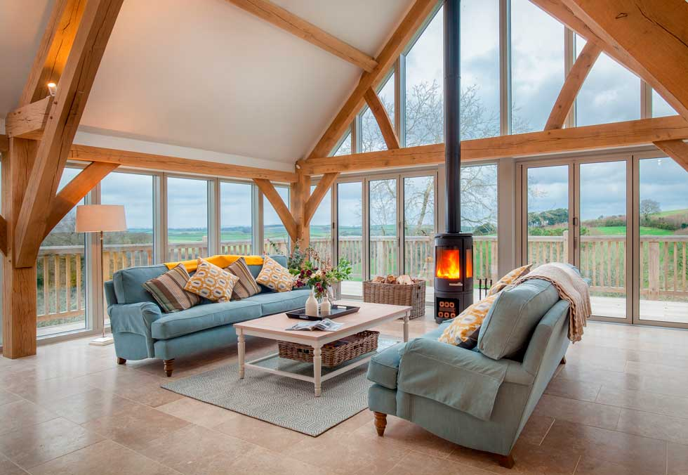 Gitcombe retreat sitting room with woodburner and expansive glazing to make the most of the surrounding views
