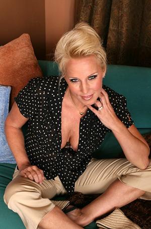Porn star TJ Hart sitting on a bed
