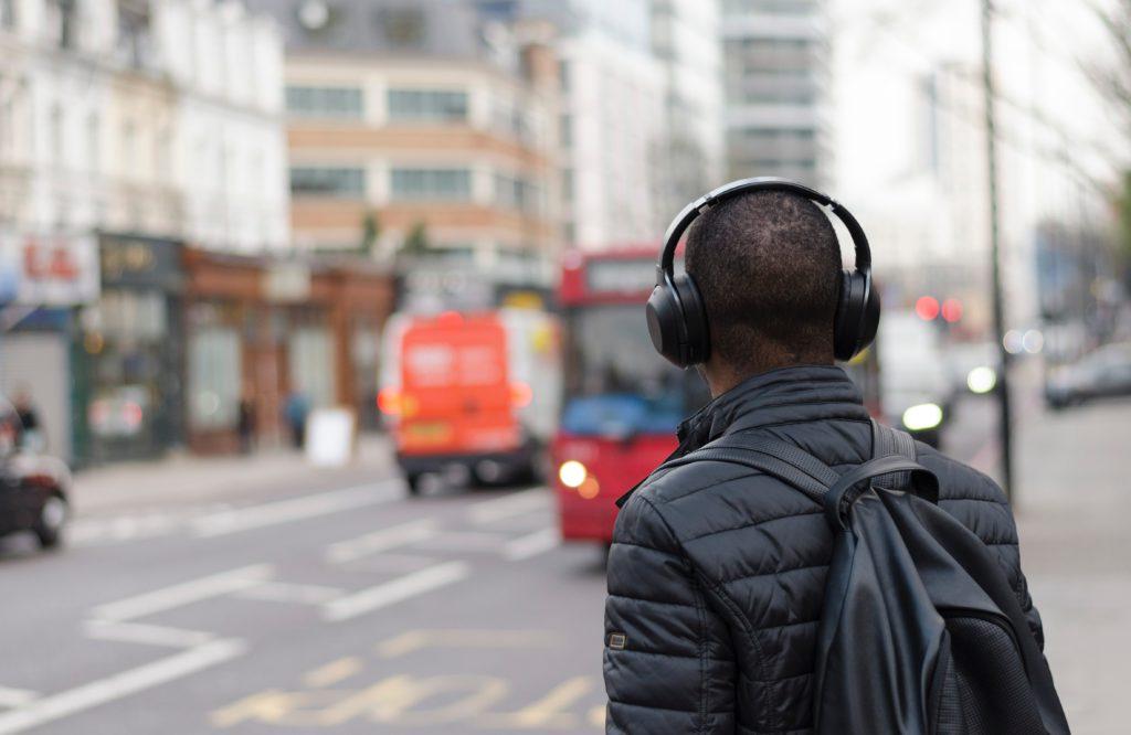 man walking on street listening to headphones