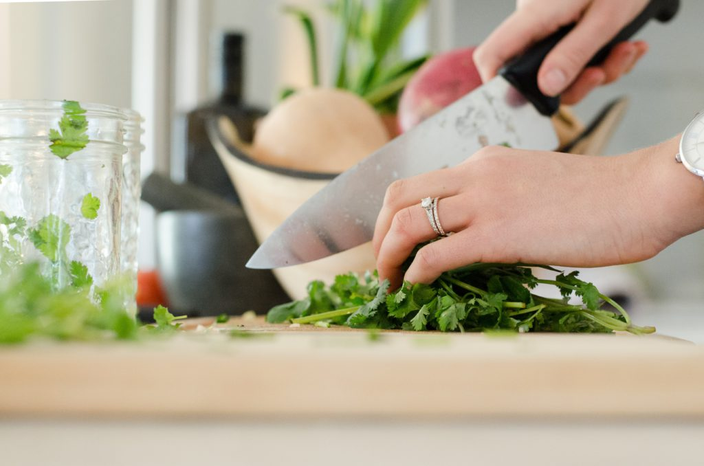 person cutting vegetables with a knife
