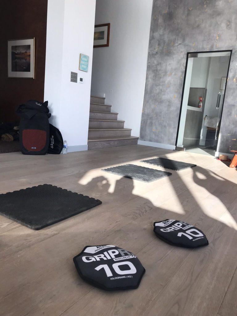 GRIPR branded excercise sandbags and floor mats on wooden floor