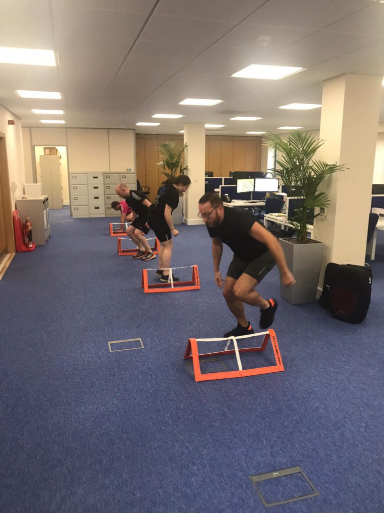 four people completing a mobile fitness course in an office