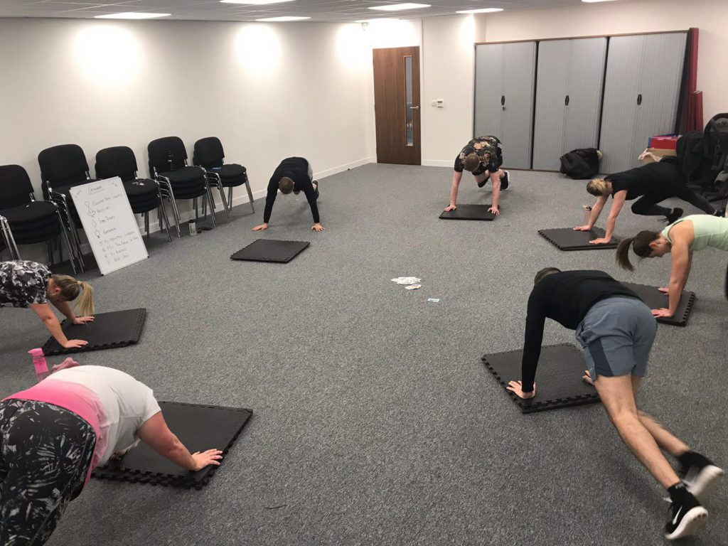 group of people doing push ups on exercise mats