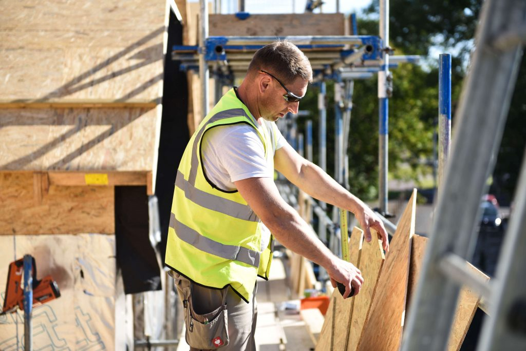 EU construction worker measuring plywood