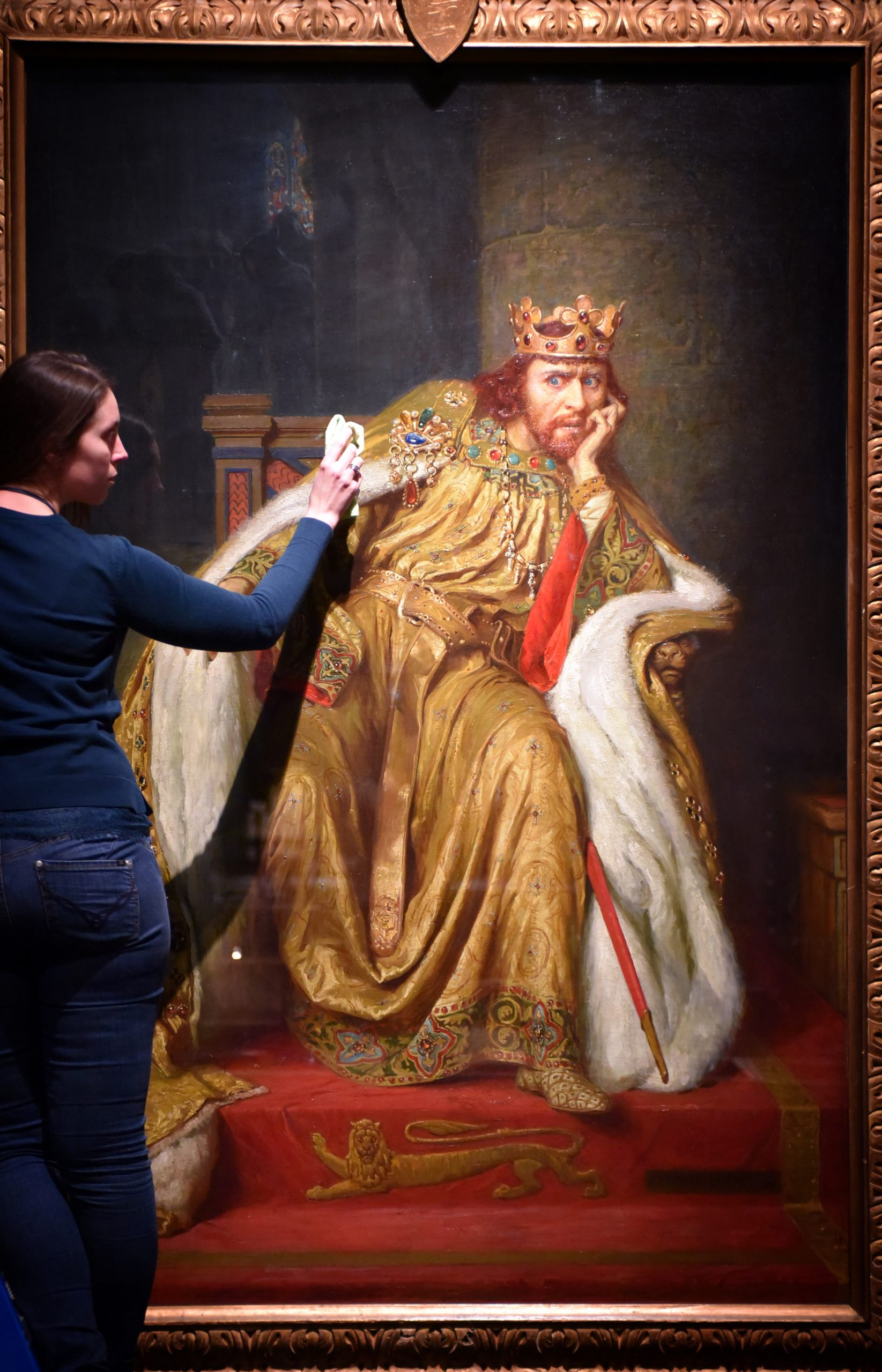 A British Library exhibition officer dusts a painting on loan from The Victoria and Albert Museum to Magna Carta- Law, Liberty, Legacy. Photography © Clare Kendall