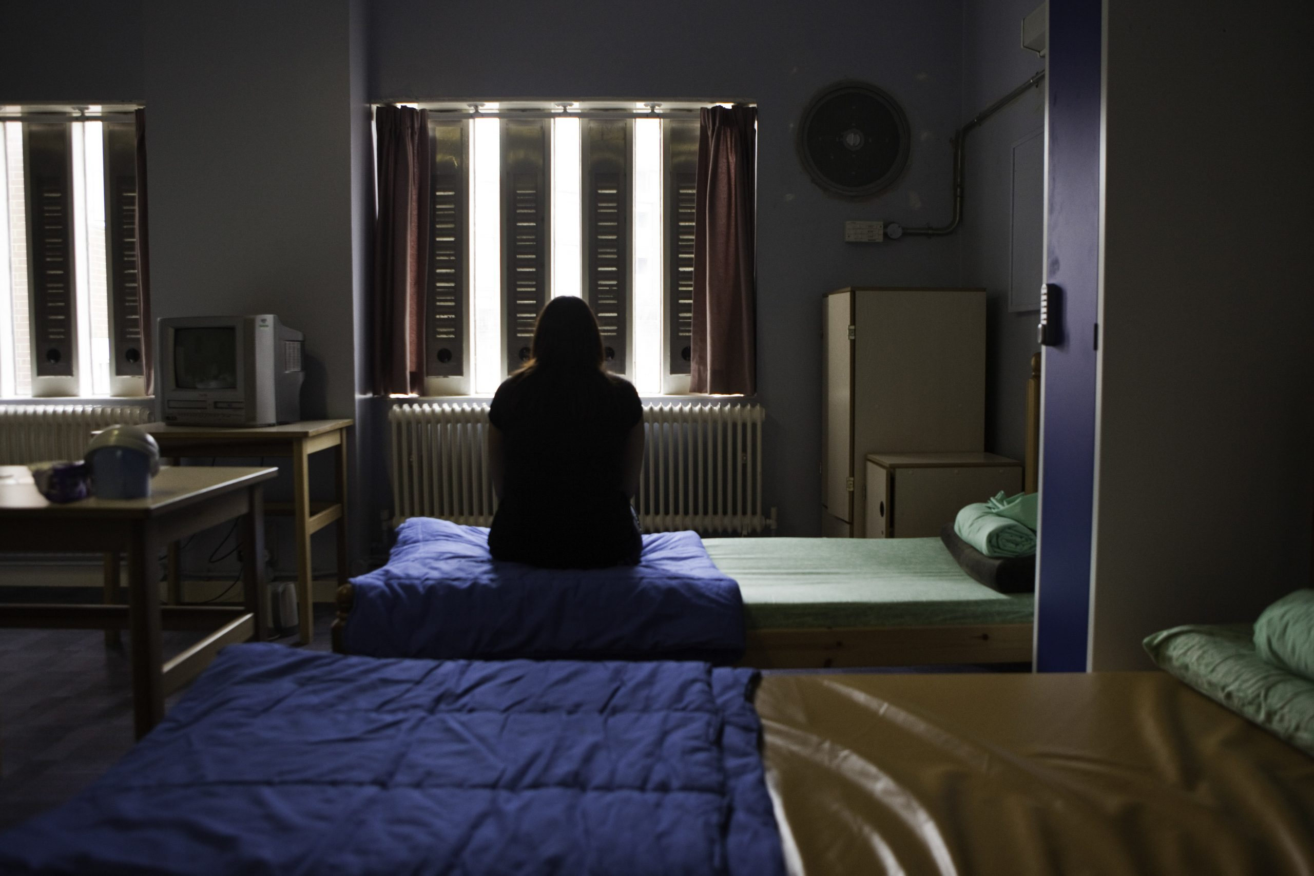 A prisoner sitting on her bed in the first night suite at HMP Holloway, the main womens prison in London.