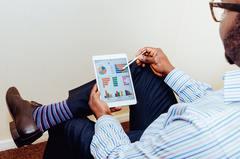 Man looking at charts on tablet