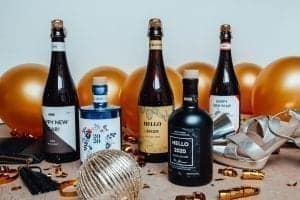 gepersonaliseerde flessen gin of bier die in een nieuwjaars setting staan