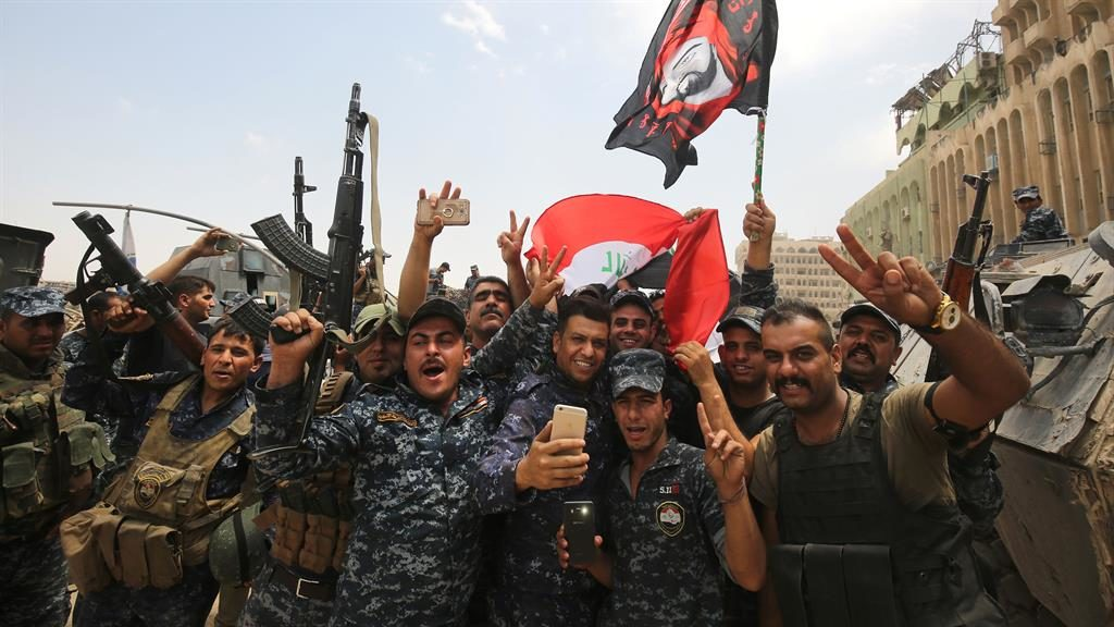 Victory Members of Iraq's defence police wave flags in celebration in Mosul's Old City yesterday