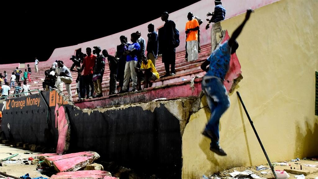 Danger: Fans near the crumbling wall in Dakar's Demba Diop stadium PICTURE: GETTY
