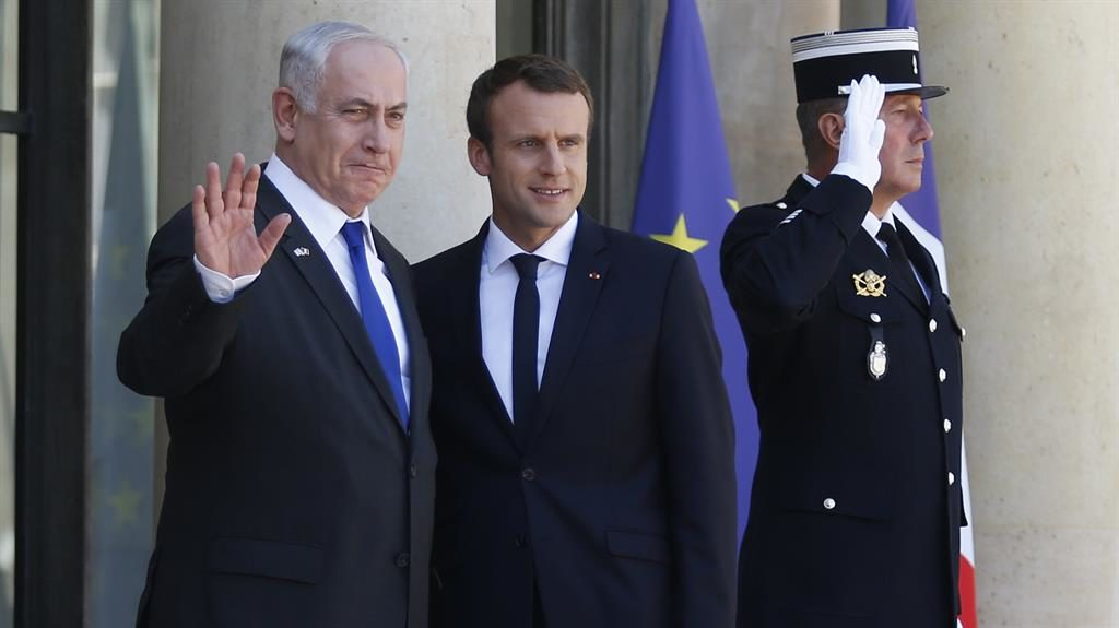 Salutes: Benjamin Netanyahu waves as he stands next to Mr Macron PICTURE: GETTY