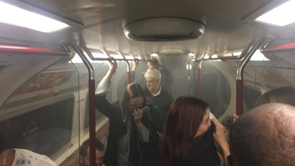 Commuters cover their mouths as smoke fills the carriage PICTURE: JOE BUNTING VIA AP
