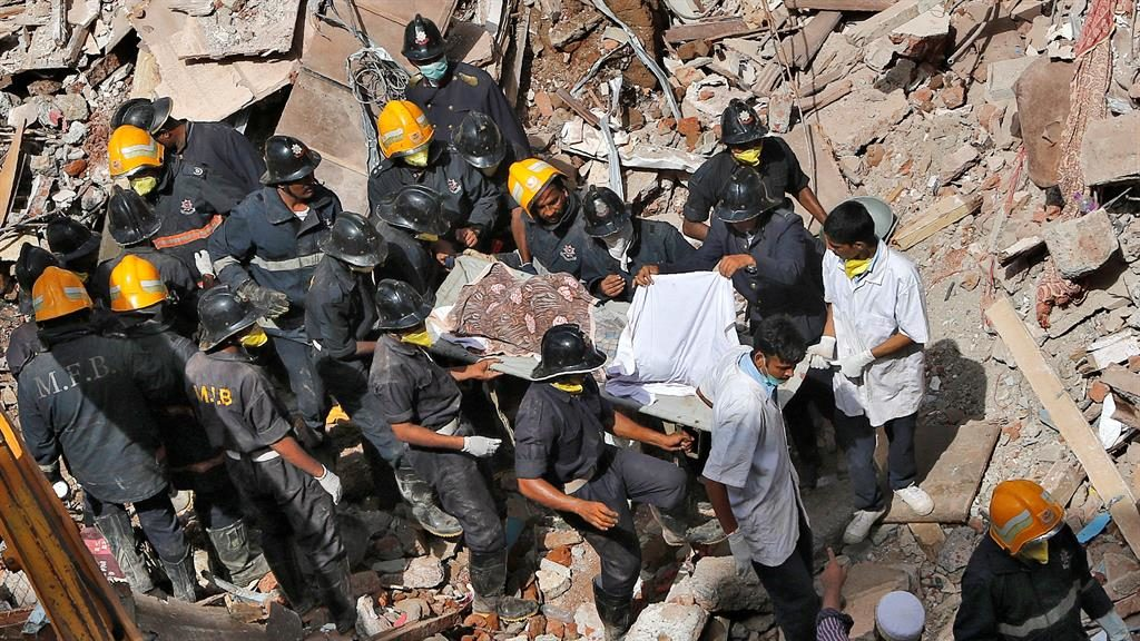 Collapse: Rescue teams carry the body of a victim from the rubble of the building in Mumbai PICTURE: REUTERS