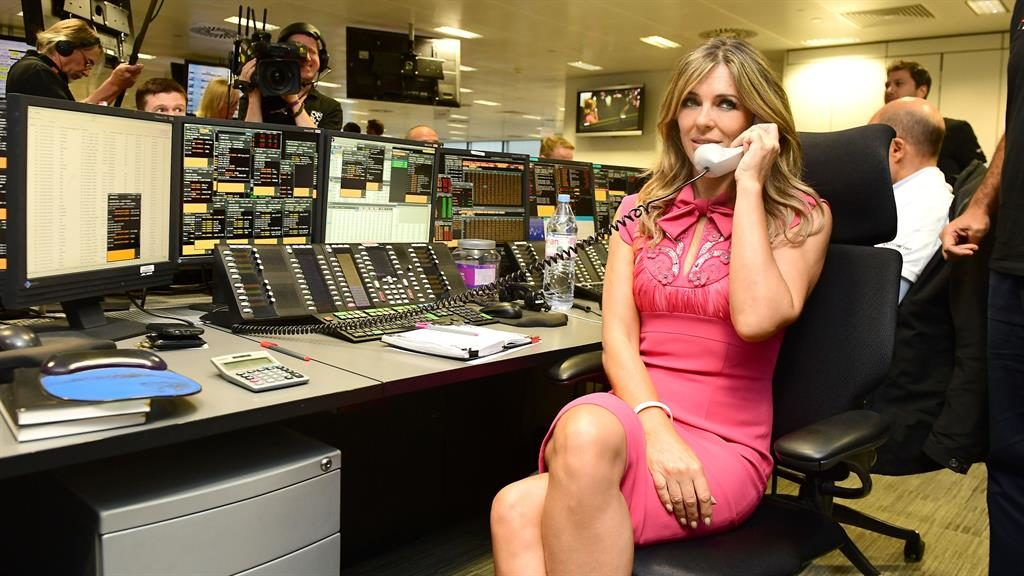 Dressed for business: Elizabeth Hurley on the phone at a trading desk in Canary Wharf