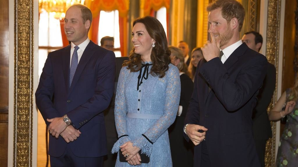 Back at work: The duke and duchess with Prince Harry at Buckingham Palace last night
