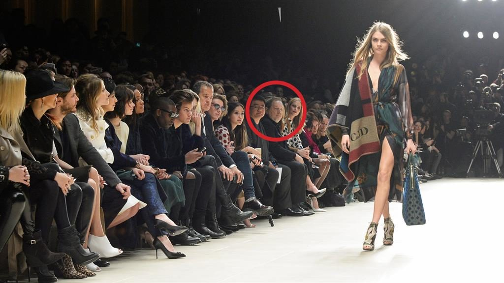 'Threatened': Cara Delevingne on the catwalk as Weinstein (circled) watches from the front row PICTURE: GETTY