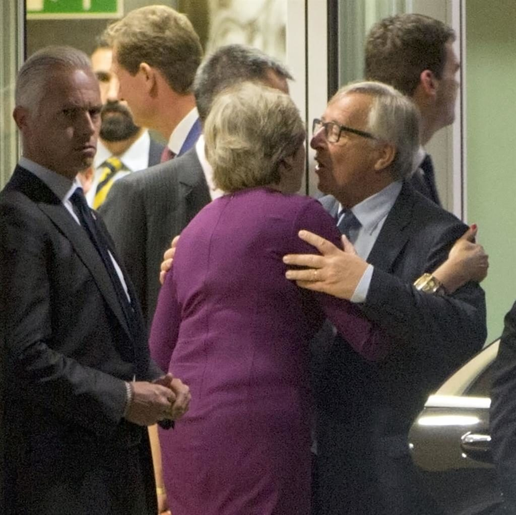 Offensive: Jean-Claude Juncker gives Theresa May a kiss after talks and (inset) grabs Brexit secretary David Davis for a hug (below) PICTURES: AP