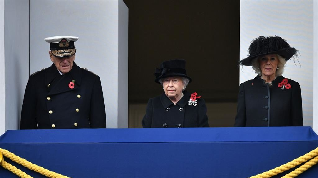 A watchful eye: The Queen observes from a balcony with the Duke of Edinburgh and Duchess of Cornwall PICTURES: EPA/PA/KARWAI TANG/REUTERS/SWNS
