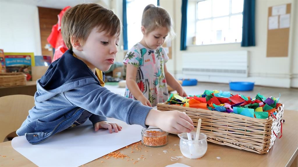 Goo for it: Pupils glue rice and lentils to paper at a Tops Day Nursery in Bournemouth PIC: PA