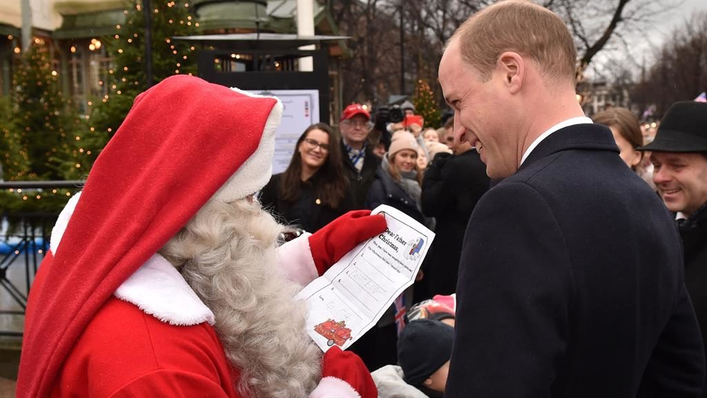 Yule better have this Prince William hands over his son's list to Santa during visit to a market in Helsinki