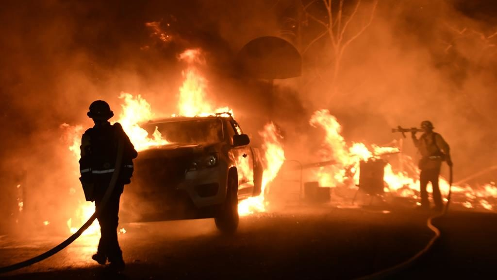 Raging: A firefighter next to a blazing car in Ventura County PICTURE: REX