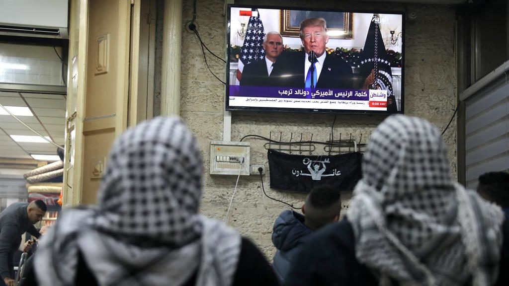 Address: Palestinians watch Mr Trump explain his decision PICTURE: REUTERS